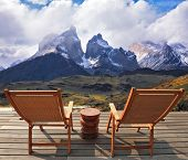 Comfortable lounge chairs on wooden platform for rest and observation. Gorgeous snow-covered rocks i