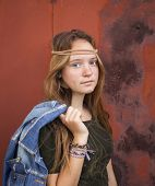 Young beautiful girl dressed in hippie style, against a background of burgundy metal wall.