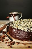Tasty chocolate cake with almond, on wooden table, on dark background