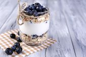 Healthy breakfast - yogurt with  blueberries and muesli served in glass jar, on color wooden background
