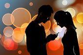 Couple using cellphone, silhouette portrait.