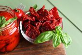 Sun dried tomatoes in glass jar, basil leaves on cutting board, on wooden background