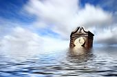picture of wispy  - Antique clock floating in water under wispy clouds - JPG