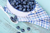 Tasty ripe blueberries in bowl, on wooden table