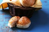 Tasty buns with sesame in wicker basket, on color wooden background