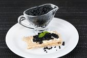 Slice of bread with butter and sauceboat with caviar on plate on dark fabric background