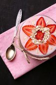 Healthy breakfast - yogurt with  strawberries and muesli served in glass jar, on wooden background