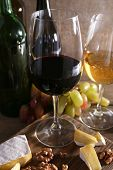 beautiful still life with wine, cheese and ripe grape on wooden background