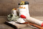 Assortment of colorful pasta in bags, rolling-pin on cutting board, on wooden background