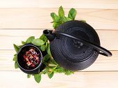 Chinese traditional teapot with fresh mint leaves and dried hibiscus petals on wooden background