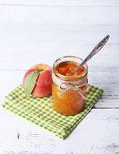 tasty peach jam with fresh peach on wooden table