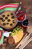 Fondue, olives, tomatoes, slices of cheese, rusks and spices on napkin on wooden background