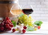 Wine with grapes on table on brick wall background