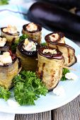 Fried aubergine with cottage cheese in a round plate on wooden background
