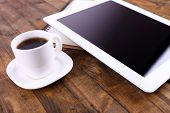 Tablet, cup of coffee and notebook on wooden background