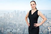 An image of a beautiful business woman in front of the big city