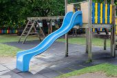 stock photo of toboggan  - Blue toboggan in the middle of a playground without children - JPG