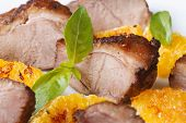 image of roast duck  - slices of roasted duck meat with orange and basil macro horizontal view from the top - JPG