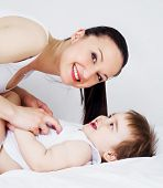 happy young mother with her baby in bed at home