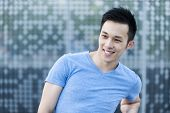 Portrait of confident young asian man smiling in urban environment with copy space