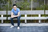 Young asian man sitting and smiling on park bench with copy space