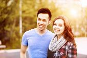 Romantic interracial young couple standing together and looking at camera outside in sunset light