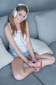 Cute pretty woman listening to her music on her headphones sitting cross-legged on a sofa smiling up