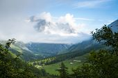 Valley in Les Ars Dessus, Switzerland, with forest and La Tsarve mountain surrounded by clouds in the background.