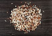 colorful blend of several varieties whole grain rice in a rustic wooden surface background