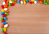 Border Frame of Colorful  JellyBeans spilled on surface wooden table. top view