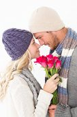 Attractive young couple in warm clothing holding flowers over white background