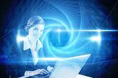 Redhead businesswoman using her laptop against blue technology design with tunnel