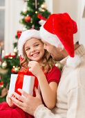family, christmas, x-mas, happiness and people concept - smiling father and daughter in santa helper