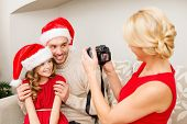 family, christmas, x-mas, happiness and people concept - mother taking picture of smiling father and