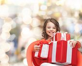 holidays, presents, christmas, childhood and people concept - smiling little girl with gift boxes ov