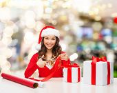 christmas, holidays, celebration, decoration and people concept - smiling woman in santa helper hat