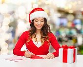 christmas, holidays, celebration, greeting and people concept - smiling woman in santa helper hat wi