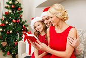 family, christmas, x-mas, happiness and people concept - smiling family in santa helper hats with many gift boxes reading book