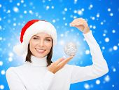 winter, people, happiness concept - woman in santa helper hat with christmas tree decoration over bl