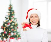 holidays, winter, happiness and people concept - smiling woman in santa helper hat holding jingle be