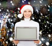 christmas, technology, winter holidays and people concept - smiling woman in santa helper hat with b