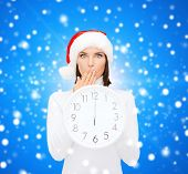 christmas, time, winter and people concept - smiling woman in santa helper hat with clock showing 12