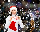 christmas, winter, happiness, holidays and people concept - smiling woman in santa helper hat with s