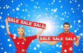 sale, shopping, christmas, holidays and people concept - smiling man and woman in red clothes with s
