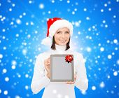 christmas, technology, present and people concept - smiling woman in santa helper hat with blank scr