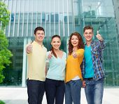 friendship, business, education and people concept - group of smiling teenagers showing thumbs up ov