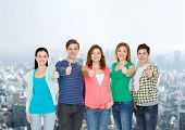 education and people concept - group of smiling students standing and showing thumbs up