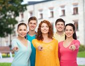 friendship, education, summer vacation and people concept - group of smiling teenagers pointing fing