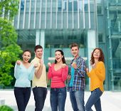 friendship, education, business, gesture and people concept - group of smiling teenagers showing tri