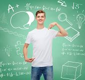 gesture, advertising, education, school and people concept - smiling young man in blank white t-shirt pointing finger on himself over green board background with doodles